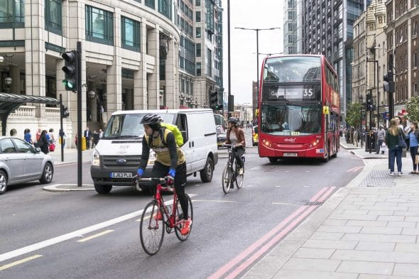 Cyclists and Modern Red London Bus