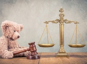 Law scales and Teddy Bear with wooden gavel