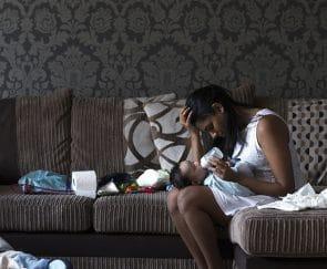 Sad single parent feeding a baby