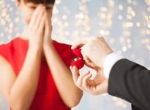 Close up of happy woman and man with engagement ring in gift box over lights background